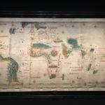 """Anonimo Portoghese Charta del navicare per le isole novamente  trovate in la parte de l'India (detta del  Cantino) 1501-02, manoscritto a inchiostro e tempera su pergamena in sei pezzi giuntati Modena, Biblioteca Estense Universitaria Fatta eseguire da Ercole I a Lisbona e portata Ferrara è la prima mappa a registrare le nuove scoperte geografiche. Nel Furioso l'Ariosto evoca il Nuovo Mondo con """"i segni imperial nel verde lito eretti"""" così come qui i vessilli di Castiglia punteggiano le verdissime coste americane."""